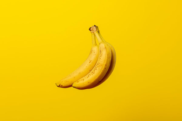 Three attached bananas are shown floating in front of a yellow background