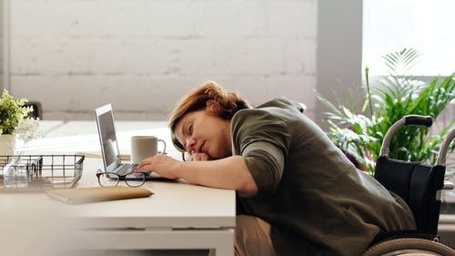 A woman rests her head at work, tired and groggy from being hungover.