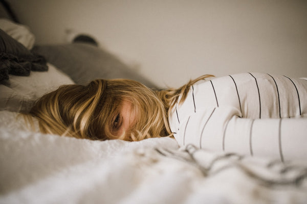 A Woman Lying on Her Front in Bed, with Face Turned Sideways, and Blonde Hair Covering All of Her Face Except One Eye