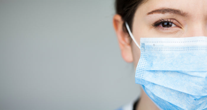 Close up of female UK EMS doctor's face,wearing blue PPE surgical protective mask