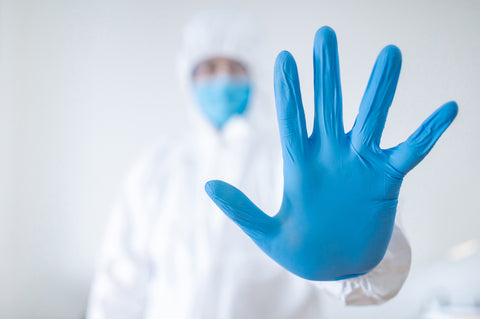 Blue rubber hand of medical worker. Preventing Coronavirus (COVID-19) infection.