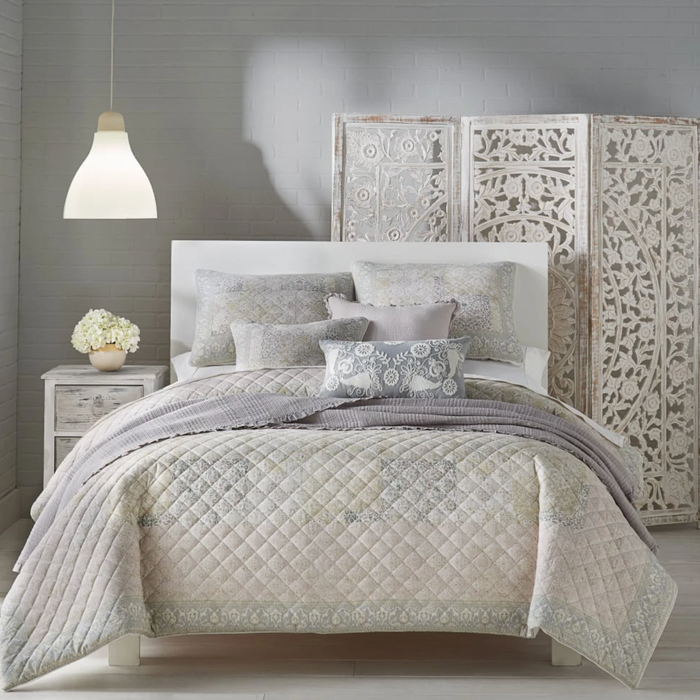 A bed layered with comfy pillows and linens from Pier 1.