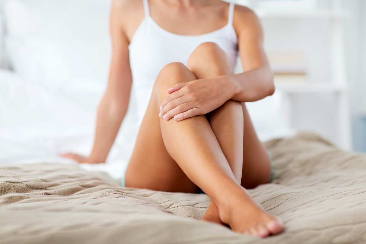 femme assise lit jambes epilees