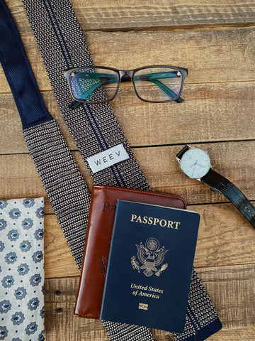 Knit Sock Tie, Watch, Passport, glasses, and other travel items on a table