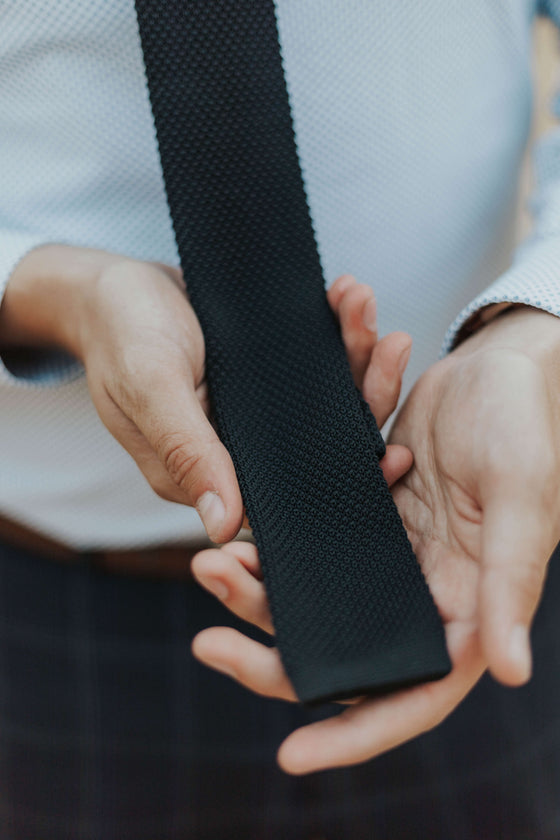 man wearing black knit tie