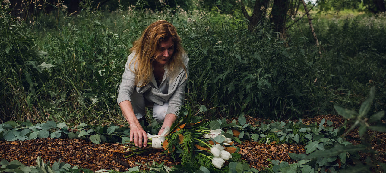 Kristin laying tulip burial spray and garland at natural burial site