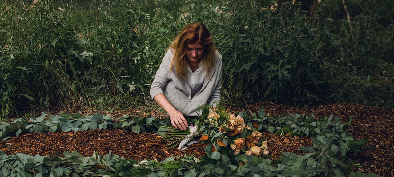 Kristin lying burial spray and garland at natural burial site
