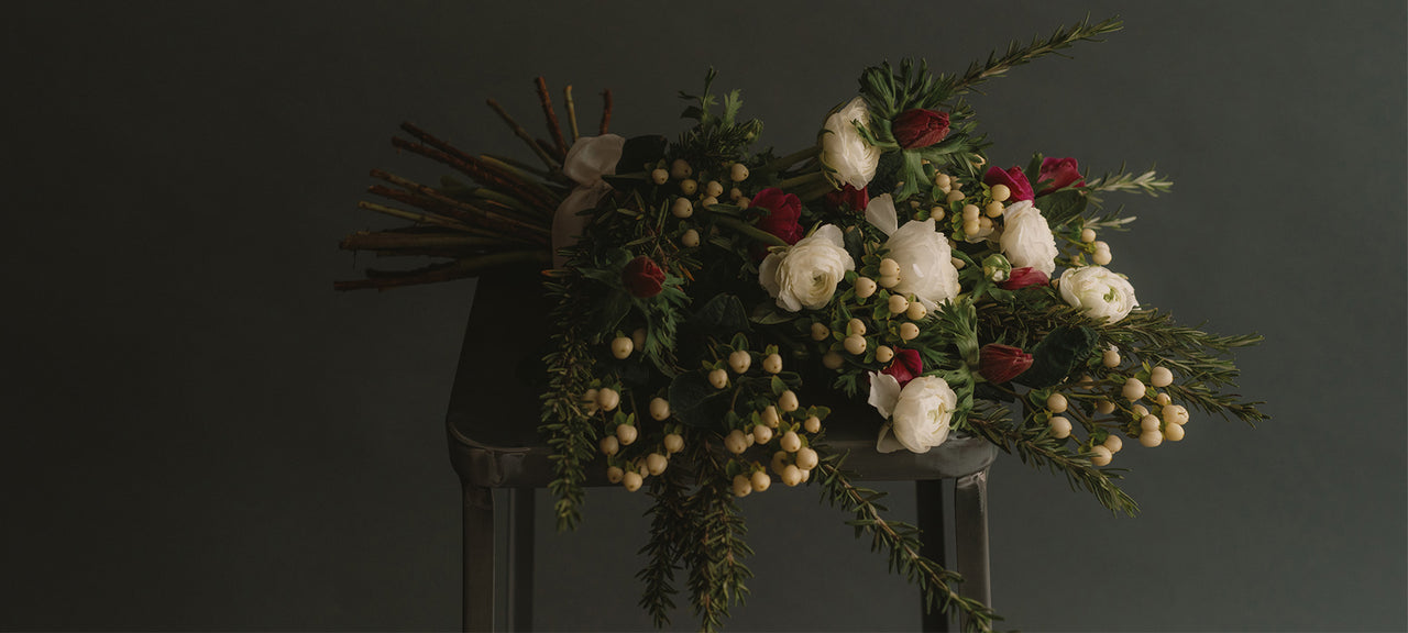 Rosemary, hypericum, bright pink and white ranunculus burial and casket spray