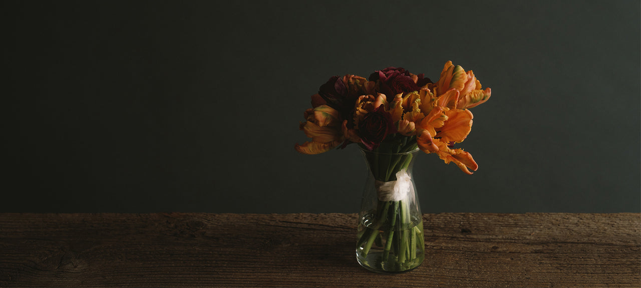Orange Parrot Tulips and bright pink ranunculus flower bouquet in a vase with raw silk ribbon