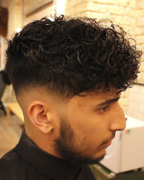 Low Skin Fade Curly Haircut With Disconnected Undercut