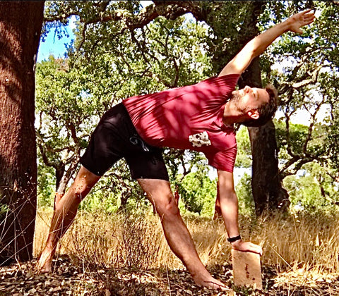 Tom practicing yoga with a handmade cork yoga block from regenerative forestry, only available at Green Blue World