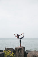 Woman doing dancer pose by the sea, wearing natural lifestyle products