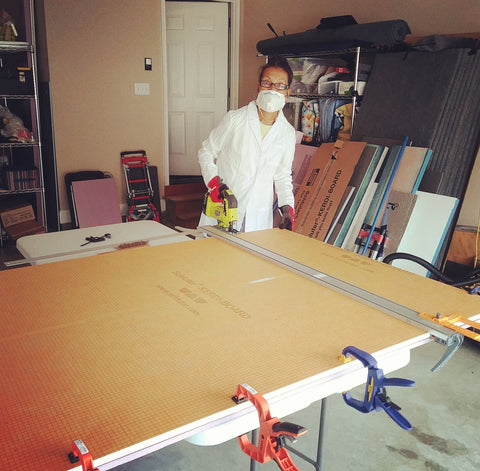 Artist Victoria Primicias wears a mask and lab coat in the garage studio while cutting a board with a jigsaw.