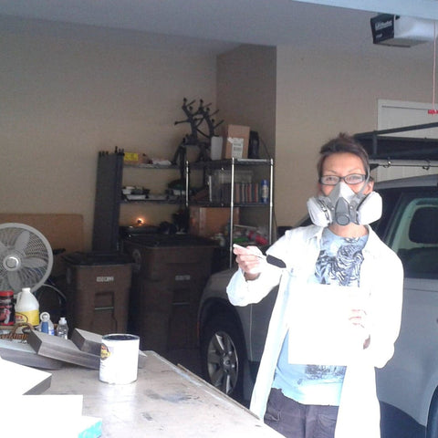 The artist in her garage studio, wearing a 3M mask and a lab coat while staining the sides of wood panels.