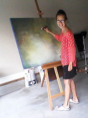 The artist, Victoria Primicias, painting at her home studio.