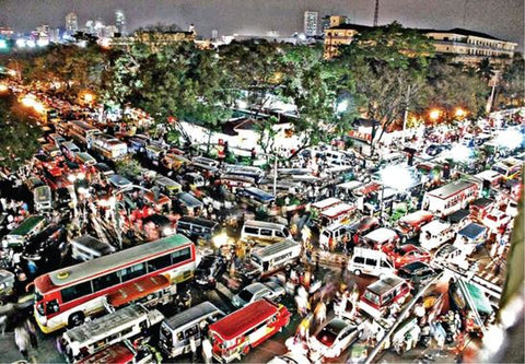 Buses and cars inch their way forward on a gridlocked corner in Manila.