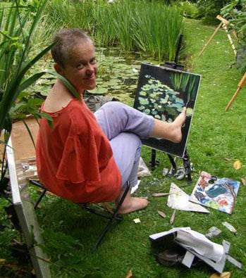 Artist Mary Duffy, at her easel, painting outdoors.