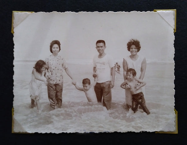 Three kids and adults in the 60s enjoying the beach in the Philippines.