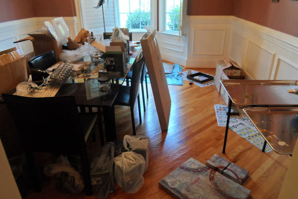 Messy artist studio takes over the entire house including the dining room.
