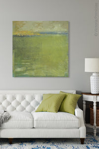"Yellow-green abstract landscape art ""Above Anything,"" metal print by Victoria Primicias, decorates the living room."