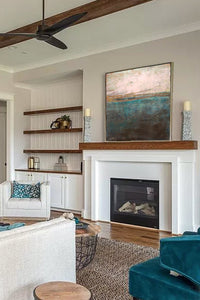 "Indigo abstract seascape painting ""Almost Forgotten,"" giclee print by Victoria Primicias, decorates the fireplace."