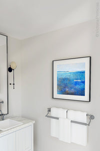 "Blue abstract coastal wall art ""Arctic Tidings,"" wall art print by Victoria Primicias, decorates the bathroom."