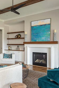 "Blue abstract beach wall art ""Beryl Basin,"" printable wall art by Victoria Primicias, decorates the fireplace."