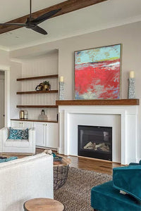 "Red abstract ocean art ""Cerise Harbor,"" metal print by Victoria Primicias, decorates the fireplace."