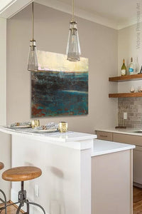"Indigo abstract beach painting ""Deep End,"" metal print by Victoria Primicias, decorates the kitchen."