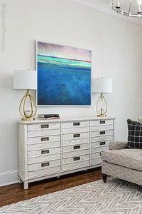 "Serene blue abstract coastal wall art ""Evening Veil,"" canvas print by Victoria Primicias, decorates the living room."