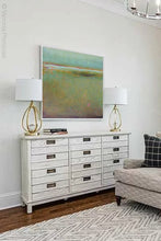 "Load image into Gallery viewer, Coastal abstract landscape painting ""Fine Margin,"" digital download by Victoria Primicias, decorates the living room."