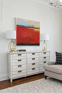 "Large red abstract coastal wall art ""Fire Sea,"" fine art print by Victoria Primicias, decorates the living room."