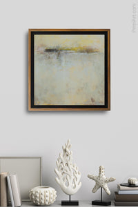 "Yellow atmospheric landscape ""Guardian Promise"" hangs on a small wall above a shelf."