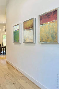 "Red and gold abstract landscape painting ""Imperial Secrets,"" wall art print by Victoria Primicias, decorates the foyer."
