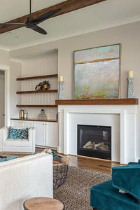 "Neutral color abstract ocean painting ""Ivory Shore,"" digital print by Victoria Primicias, decorates the fireplace."