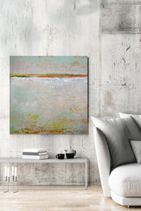 "Neutral color abstract ocean painting ""Ivory Shore,"" digital print by Victoria Primicias, decorates the living room."