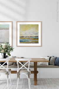 "Coastal landscape painting ""Lapping Layers,"" digital download by Victoria Primicias, decorates the dining room."