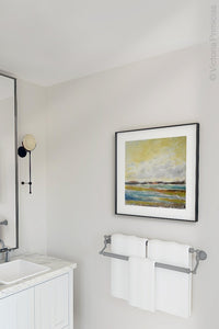 "Yellow coastal abstract landscape art ""Lapping Layers,"" canvas print by Victoria Primicias, decorates the bathroom."