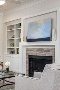 "Blue horizon abstract landscape ""Local Celebrity"" 24x36 in. sits on a fireplace mantel."