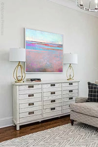 "Pink abstract beach art ""Marathon Miles,"" canvas print by Victoria Primicias, decorates the living room."