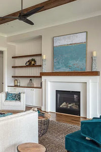 "Bluegreen abstract ocean paintings ""Merchant Crossing,"" canvas print by Victoria Primicias, decorates the fireplace."