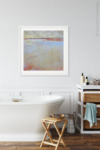 "Contemporary coastal abstract landscape art ""Migrant Shores,"" metal print by Victoria Primicias, decorates the bathroom."