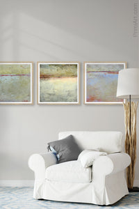 "Contemporary coastal abstract landscape art ""Migrant Shores,"" metal print by Victoria Primicias, decorates the living room."