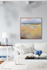 "Yellow abstract ocean wall art ""Morning Gallery,"" metal print by Victoria Primicias, decorates the living room."