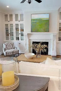 "Square contemporary abstract landscape painting ""Peridot Pastures,"" printable wall art by Victoria Primicias, decorates the living room."