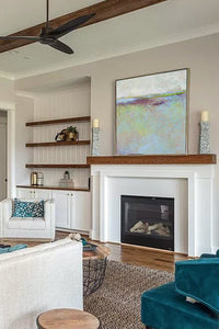"Large abstract beach painting ""Plum Passages,"" metal print by Victoria Primicias, decorates the fireplace."