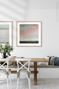 "Large abstract coastal wall art ""Retiring Sky,"" digital art landscape by Victoria Primicias, decorates the dining room."