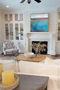 "Turquoise blue abstract coastal wall art ""Rising Tides,"" original art painting by Victoria Primicias, hangs above the fireplace."