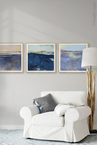 "Indigo blue abstract ocean wall art ""Secret Waters,"" digital art landscape by Victoria Primicias, decorates the living room."