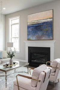 "Indigo blue abstract landscape painting ""Secret Waters,"" wall art print by Victoria Primicias, decorates the fireplace."